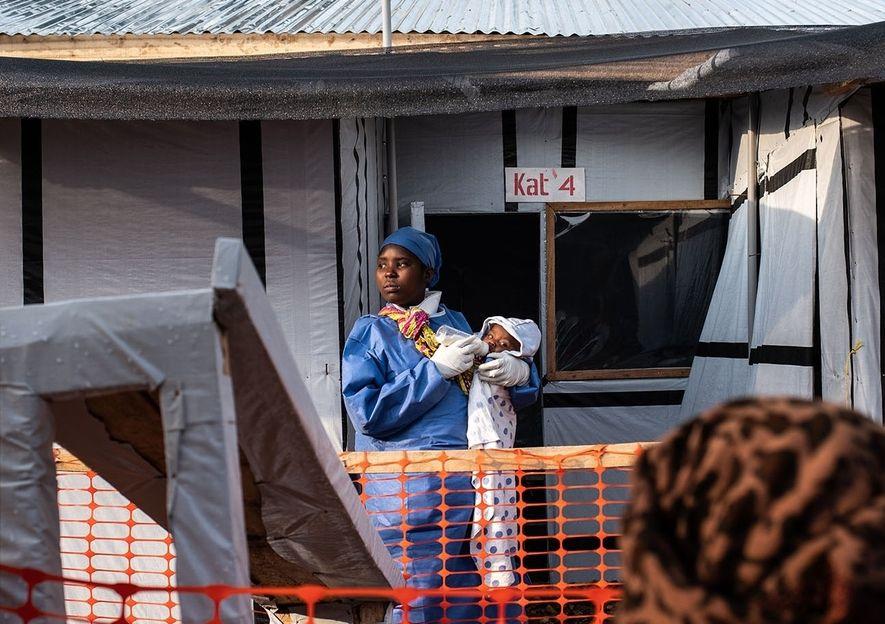 A sobrevivente do Ébola, Sylvie Kyakinwa, de 18 anos, segura Kavira Joyeuse, de 7 meses, enquanto a sua mãe assiste atrás da linha designada para os visitantes, no centro de tratamento em Butembo. Os sobreviventes do Ébola não são suscetíveis ao vírus, por isso, alguns acabam por cuidar de crianças mais pequenas, fornecendo a atenção de que precisam na ausência dos pais.