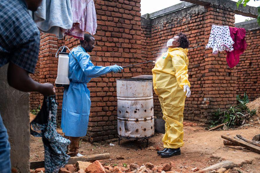 Depois de levar um caso suspeito de Ébola para uma ambulância em espera, uma profissional de saúde é borrifada com água clorada, antes de poder remover o seu equipamento de proteção individual.