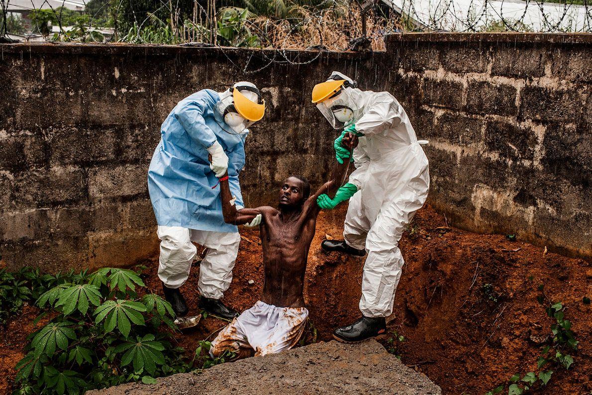 A equipa médica do Centro Hastings de Tratamento de Ébola, na Serra Leoa, ajuda um homem ...