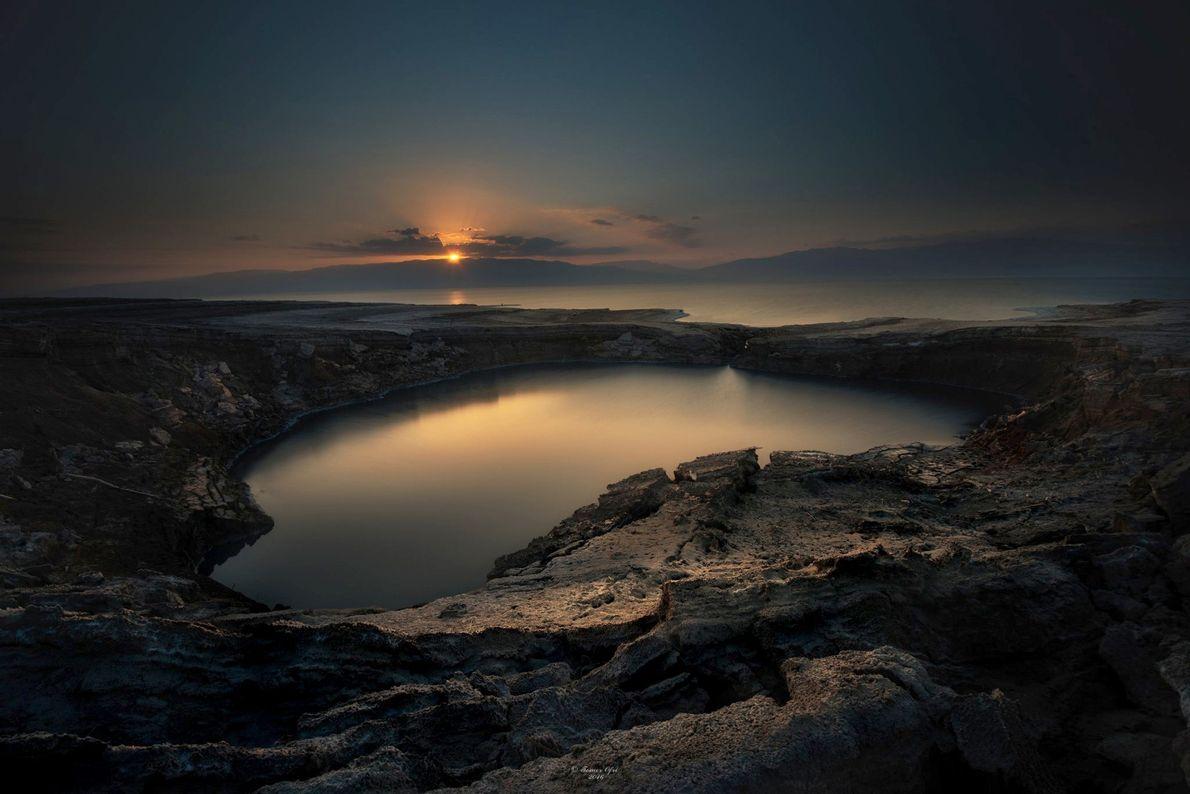O sol da manhã a deslizar entre as nuvens, sobre uma espécie de cratera, nas margens ...