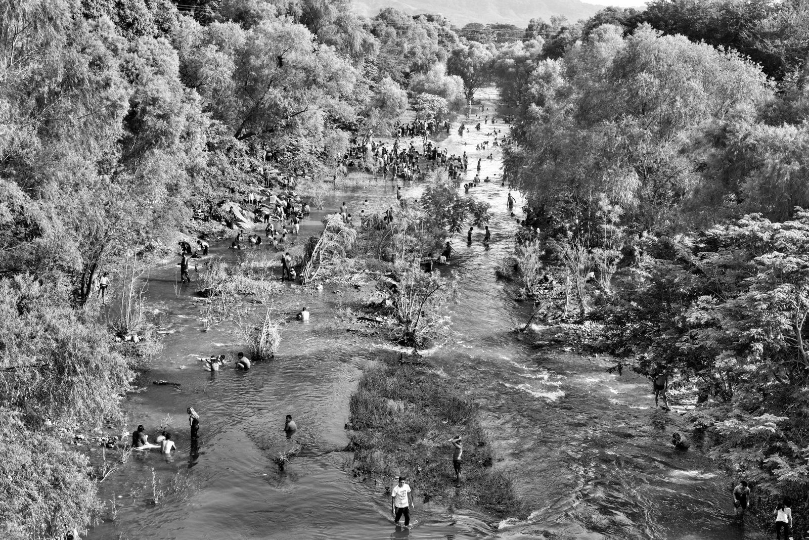 Centenas de migrantes da América Central aproveitam para se refrescar, para tomar banho e limpar as ...