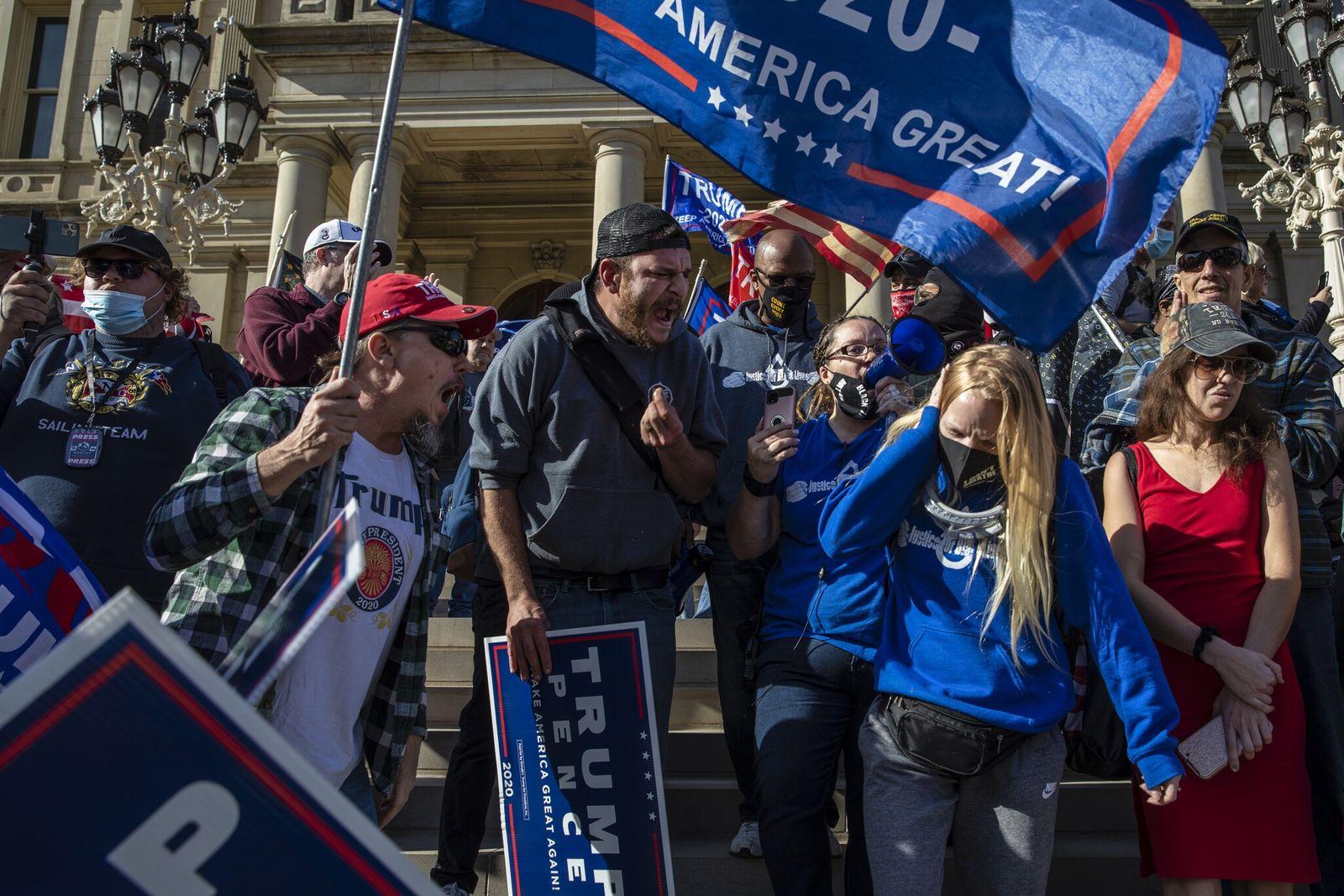Nos degraus do Capitólio do Estado de Michigan, em Lansing, os apoiantes de Trump gritaram com ...