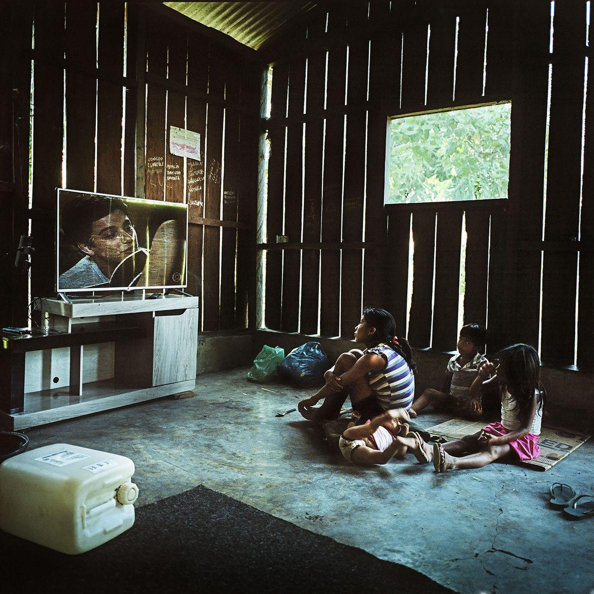 Uma família Munduruku vê telenovelas brasileiras na aldeia de Sawre Muybu