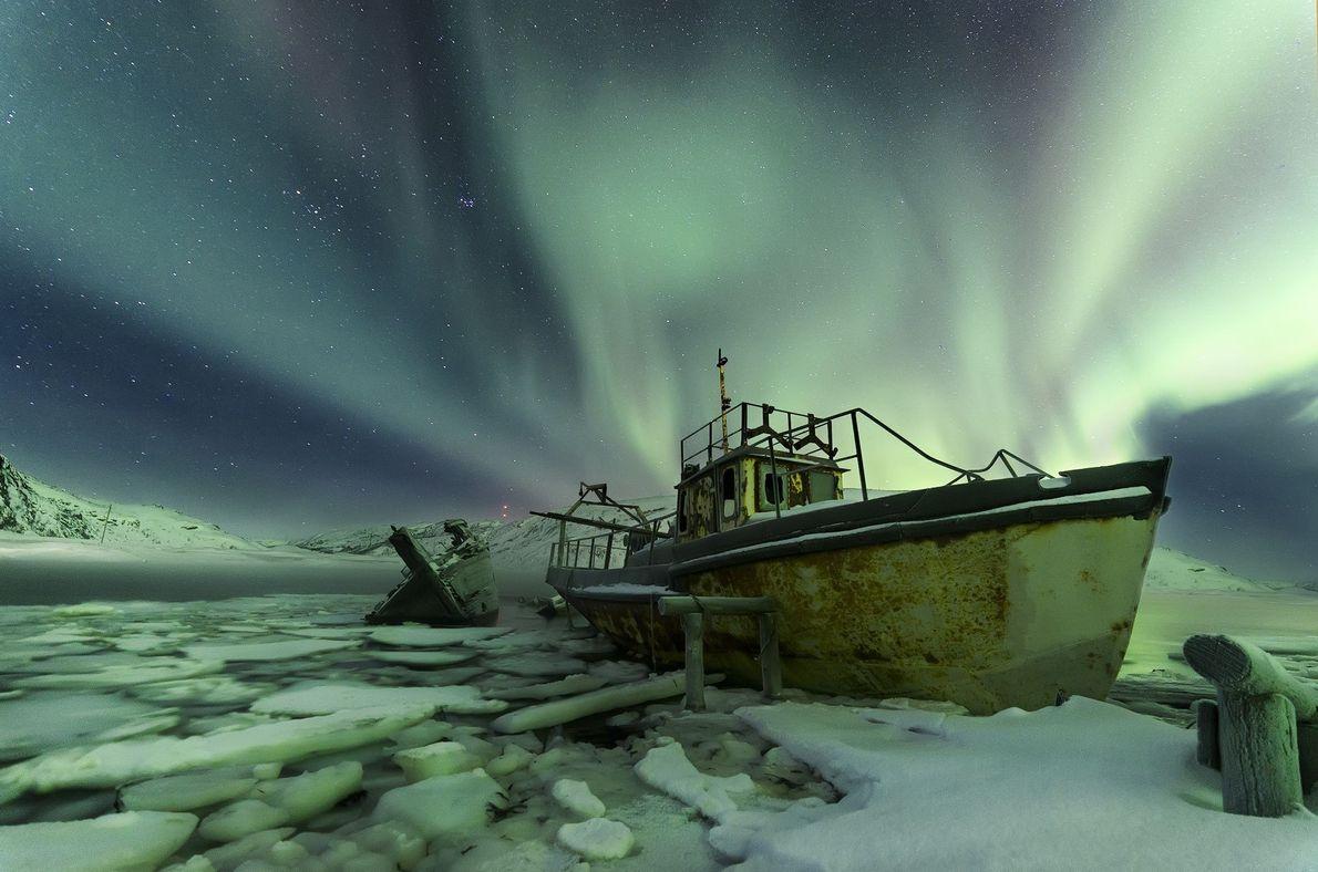 A aurora boreal brilha através de navios velhos, abandonados na aldeia de Teriberka, na Rússia