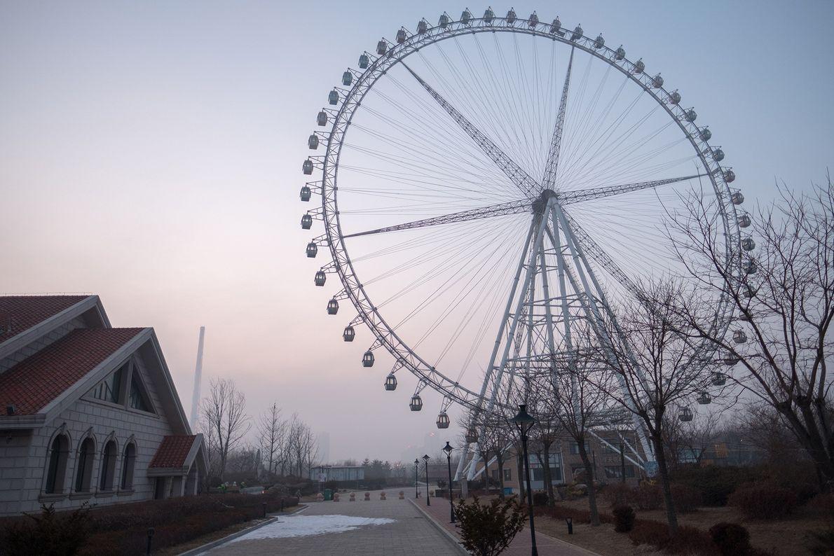 Uma roda-gigante vazia ergue-se sobre um extenso empreendimento imobiliário, no exterior de Dandong, na China