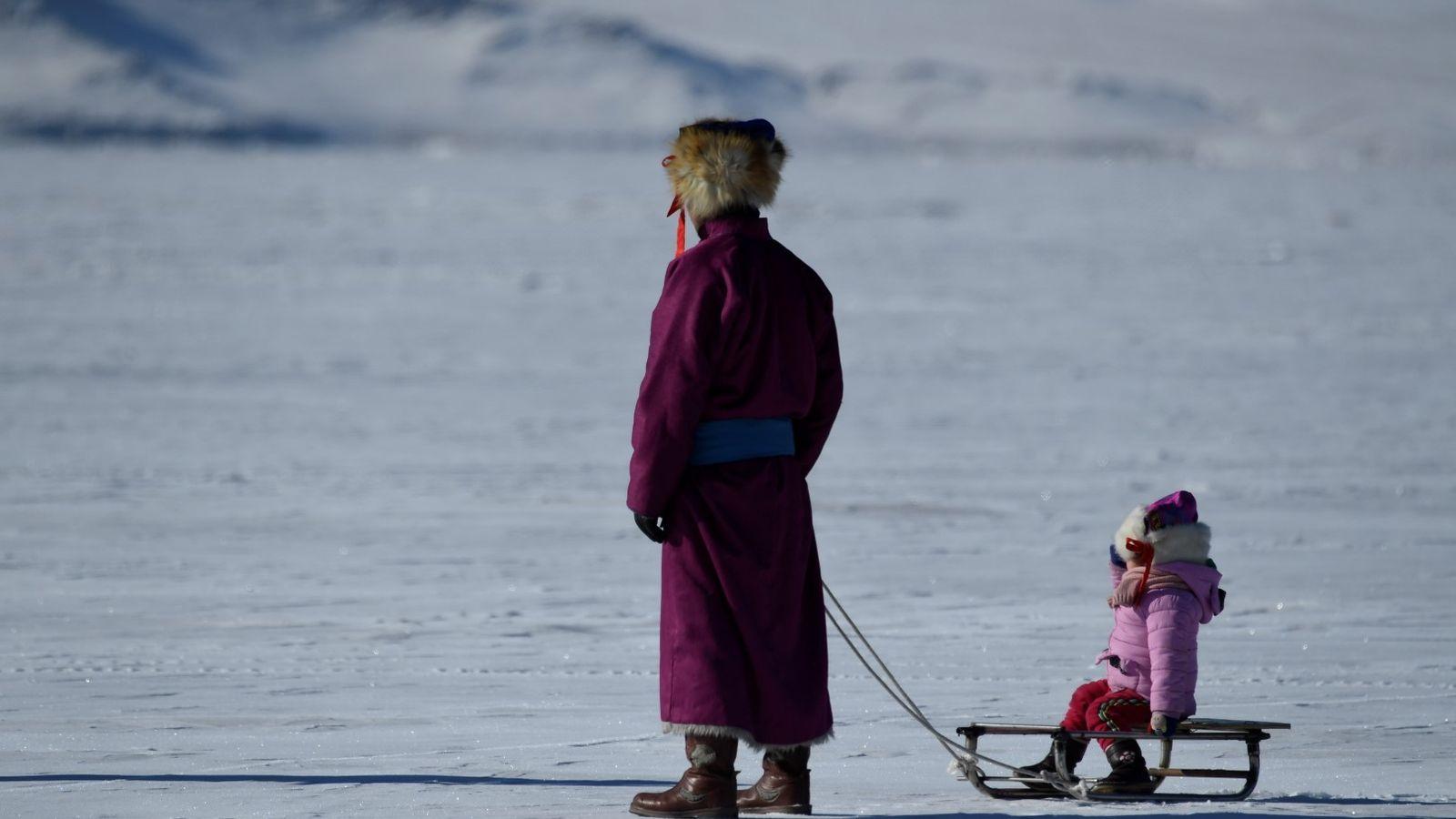 Família chega para as festividades dos jogos no gelo nas montanhas Altai da Mongólia.