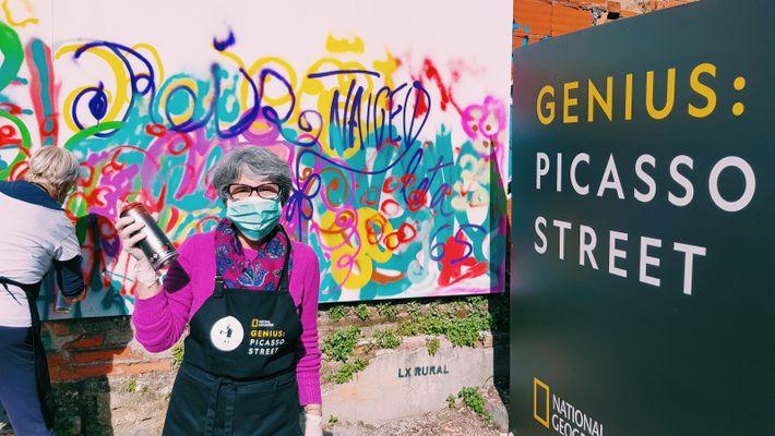 Idosa exibe lata de tinta junto a uma parede de graffiti