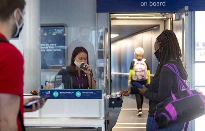 Uma agente de embarque da United Airlines ajuda os passageiros protegida por um escudo de plástico ...