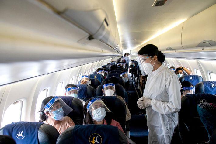 Uma assistente de bordo da companhia Buddha Air usa um fato de proteção individual e viseira ...