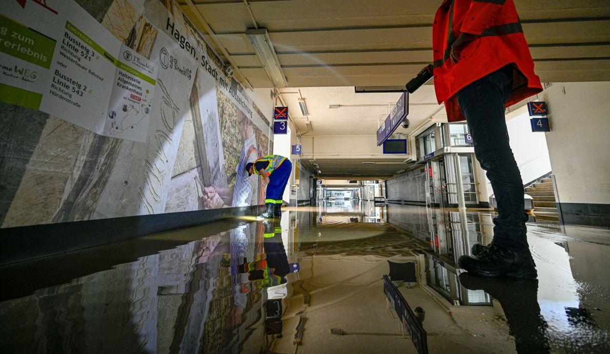 Um membro da THW (Agência Federal de Auxílio Técnico) limpa uma passagem subterrânea inundada numa estação ...
