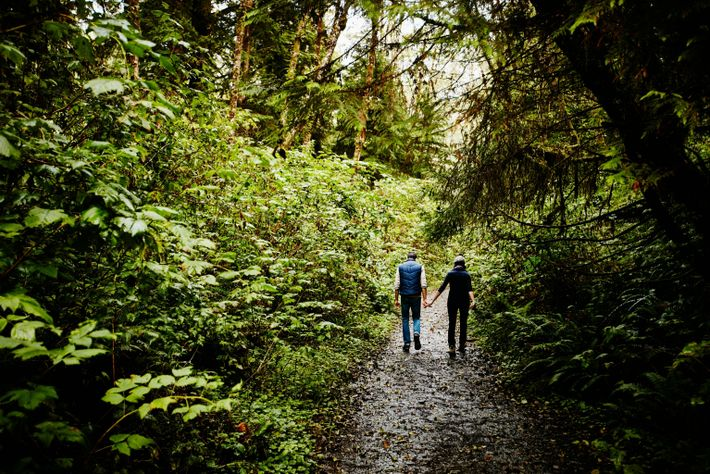 Couple holding hands hiking on a muddy trail through woods in Washington