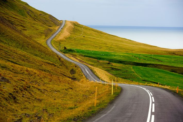Uma estrada serpenteia por um fiorde perto da vila de Siglufjörður, na Arctic Coast Way. Esta ...