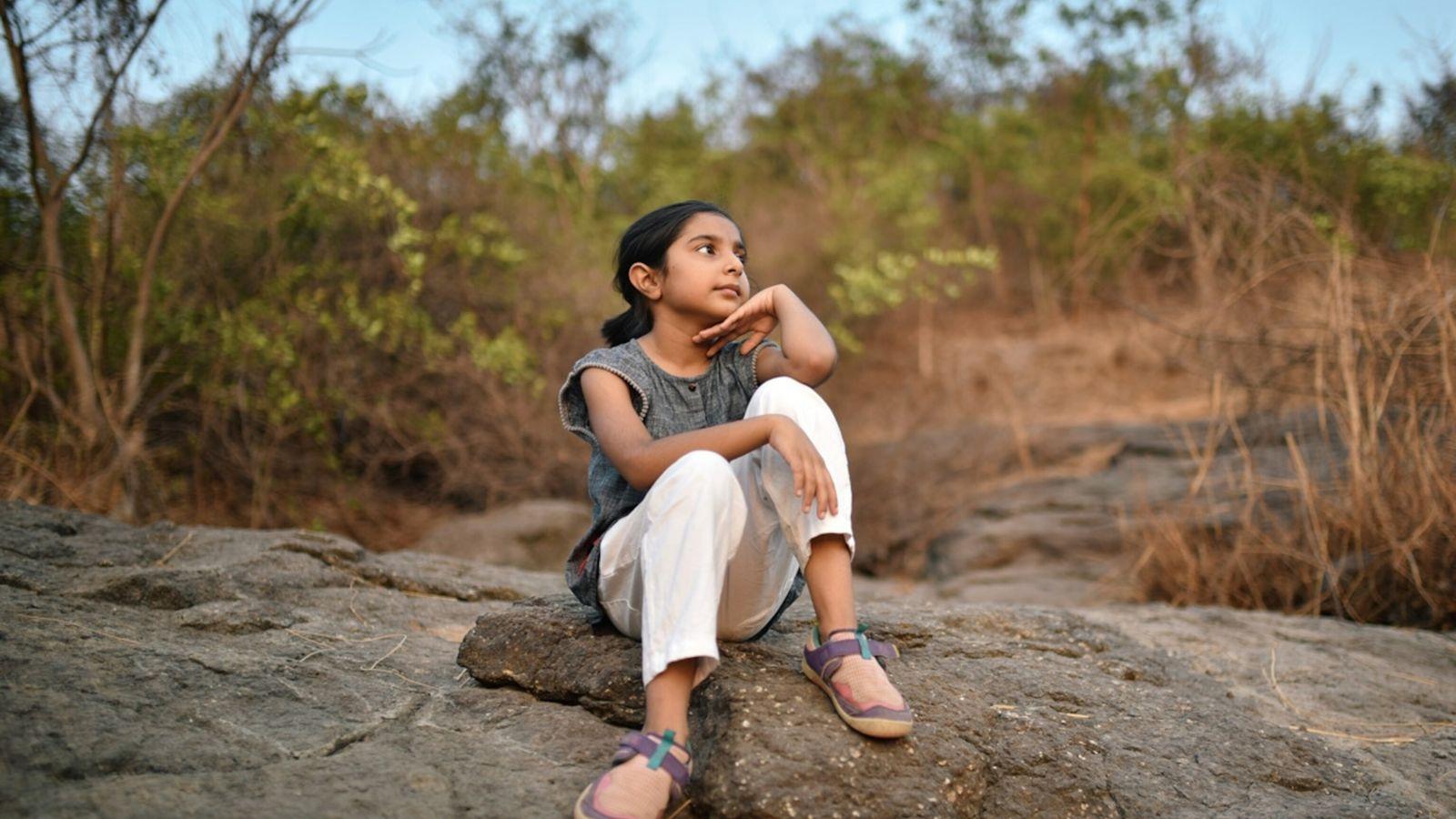 Criança sentada em silêncio na natureza