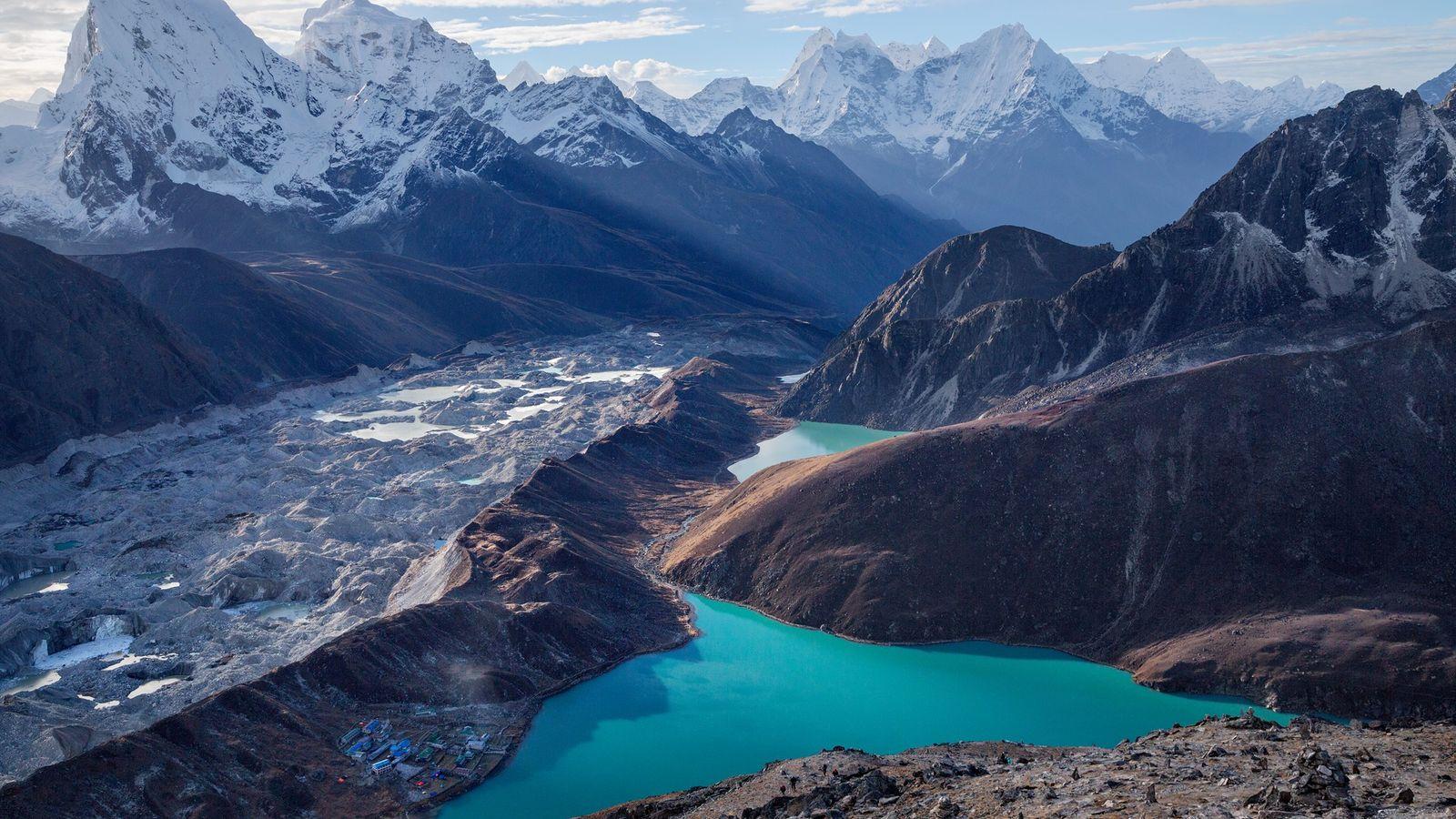A aldeia de Gokyo, encaixada junto de um lago parcialmentealimentado pelo glaciar Ngozumba, no Nepal, não ...