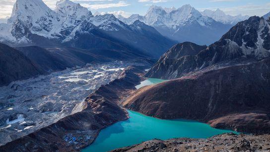 A aldeia de Gokyo, encaixada junto de um lago parcialmente alimentado pelo glaciar Ngozumba, no Nepal, não ...