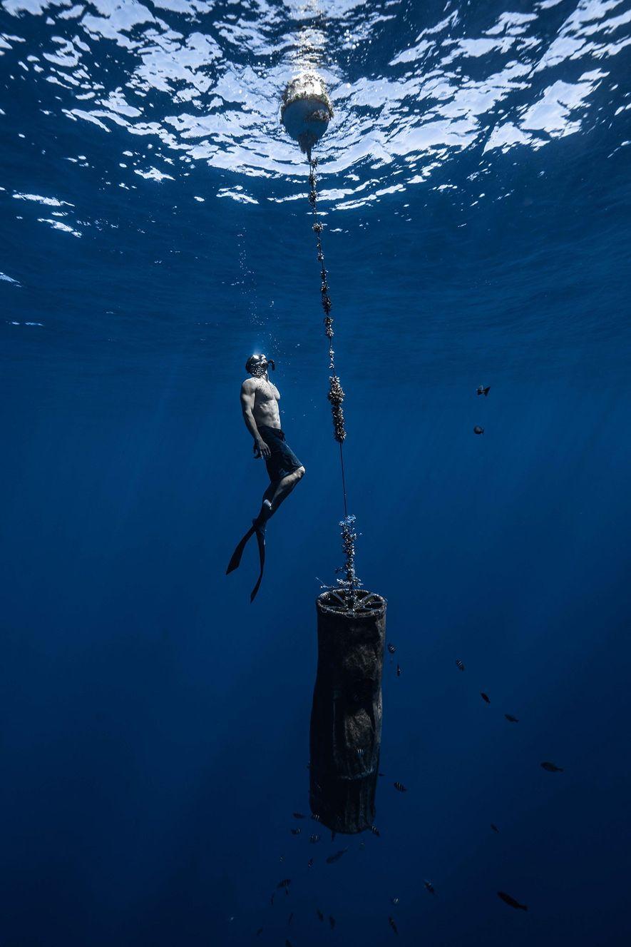 """Um membro da equipa de Lecomte inspeciona o """"Drifter C"""", uma boia usada pelos cientistas para rastrear o movimento da Grande Ilha de Lixo do Pacífico."""