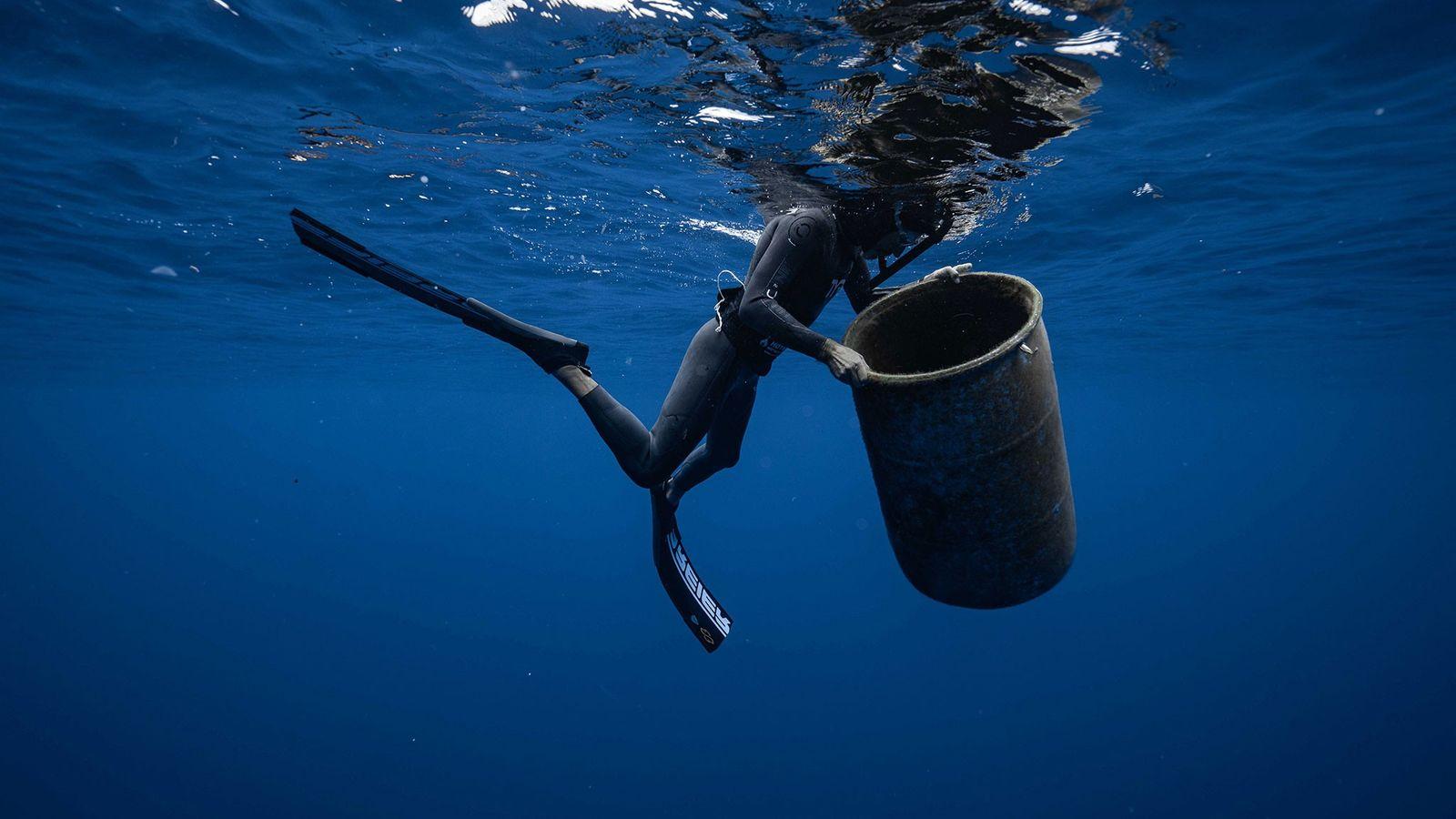 Ben Lecomte, nadador de longa distância, com um contentor de lixo encontrado na Grande Ilha de ...
