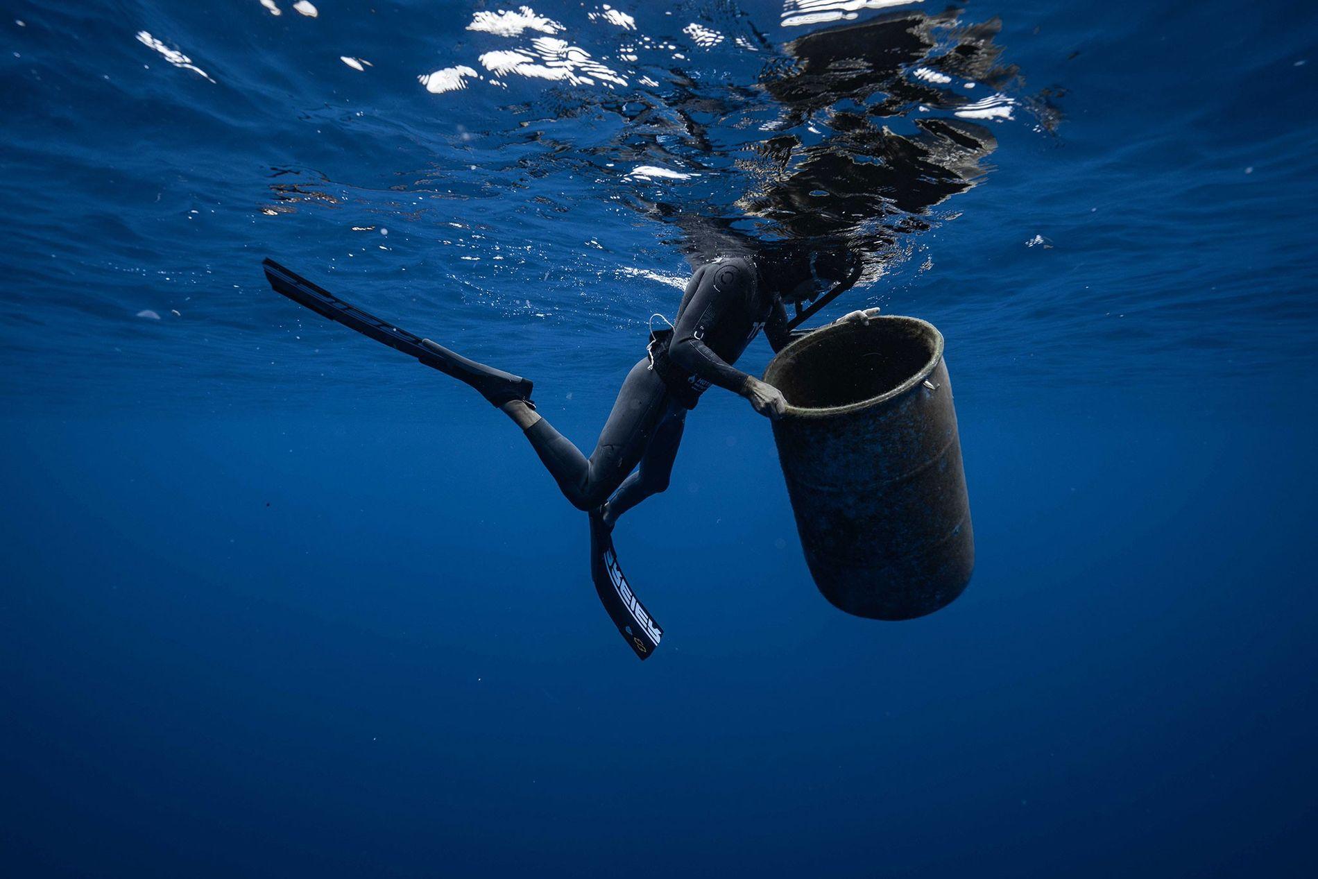 Ben Lecomte, nadador de longa distância, com um contentor de lixo encontrado na Grande Ilha de Lixo do Pacífico, um vórtice maciço de lixo plástico no Oceano Pacífico, entre a Califórnia e o Havai. Lecomte está a nadar no lixo para ajudar a recolher amostras de microplástico.