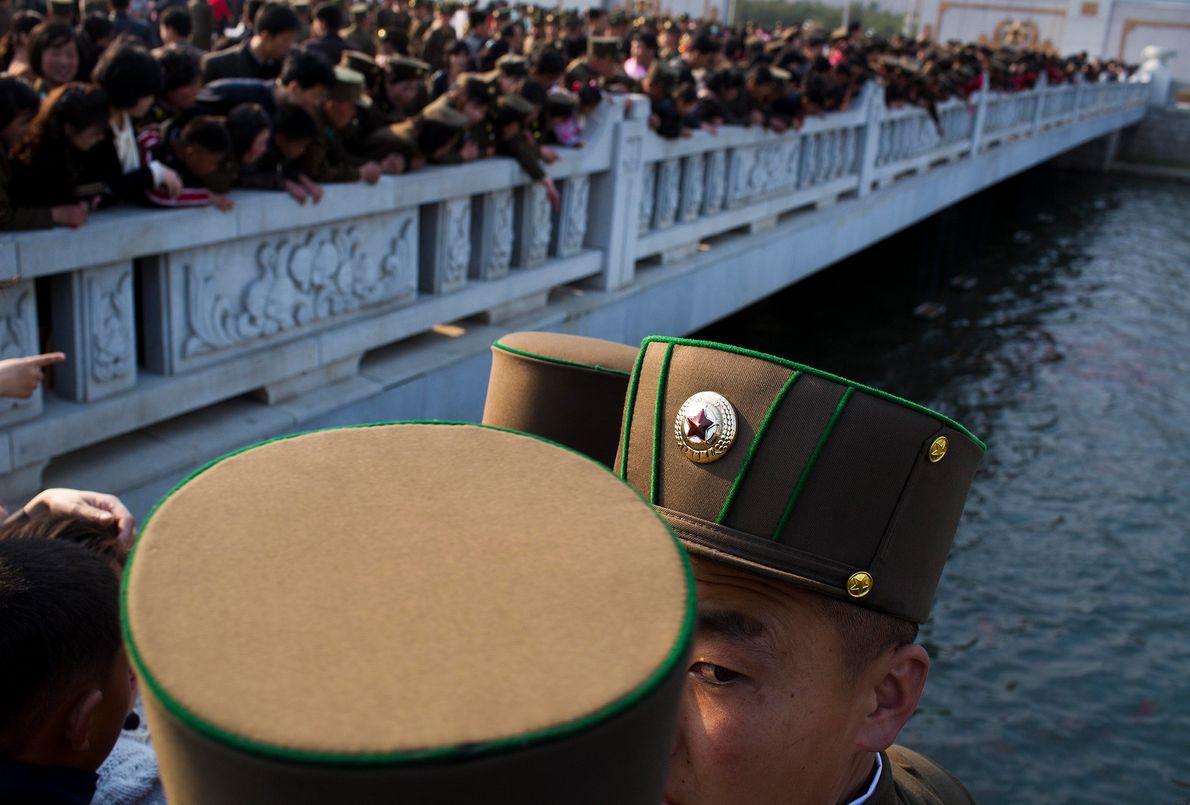 Soldados e civis norte-coreanos de pé sobre uma ponte pedonal observam os peixes-dourados do fosso
