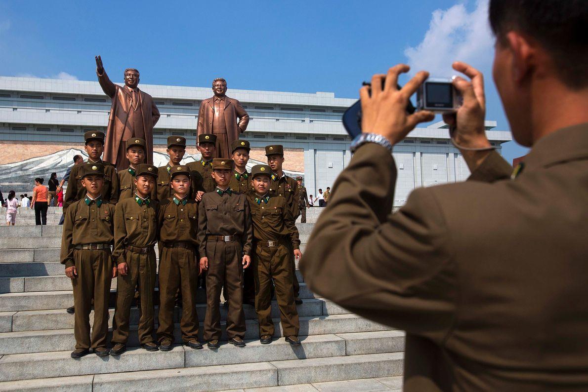 Soldados norte-coreanos posam para uma fotografia, em frente das estátuas de bronze dos falecidos líderes Kim ...