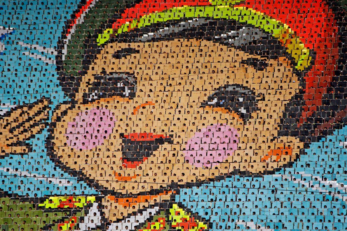 Os norte-coreanos viram páginas de livros coloridos para criar um mosaico gigante