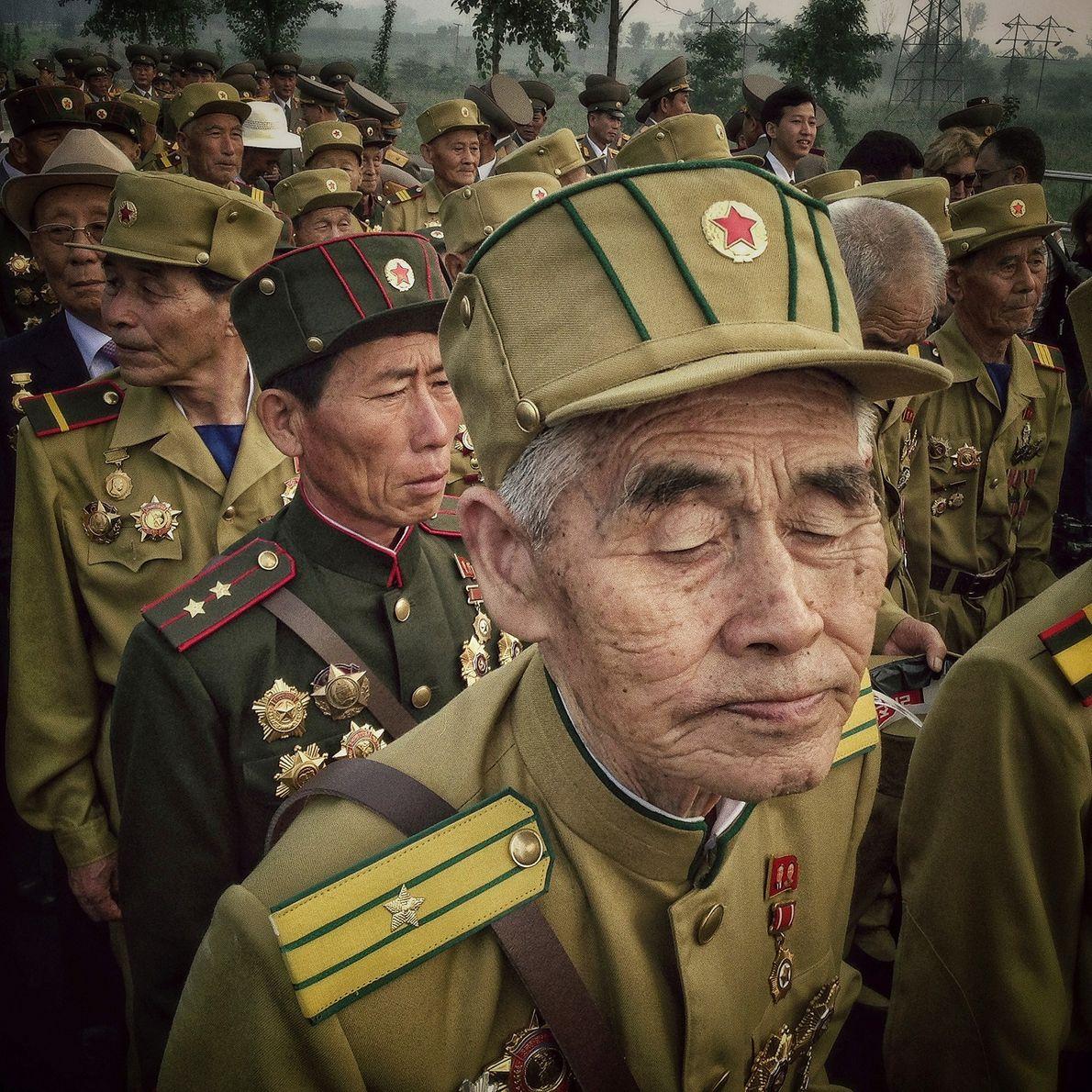 Os veteranos norte-coreanos da guerra da Coreia entram num cemitério para veteranos