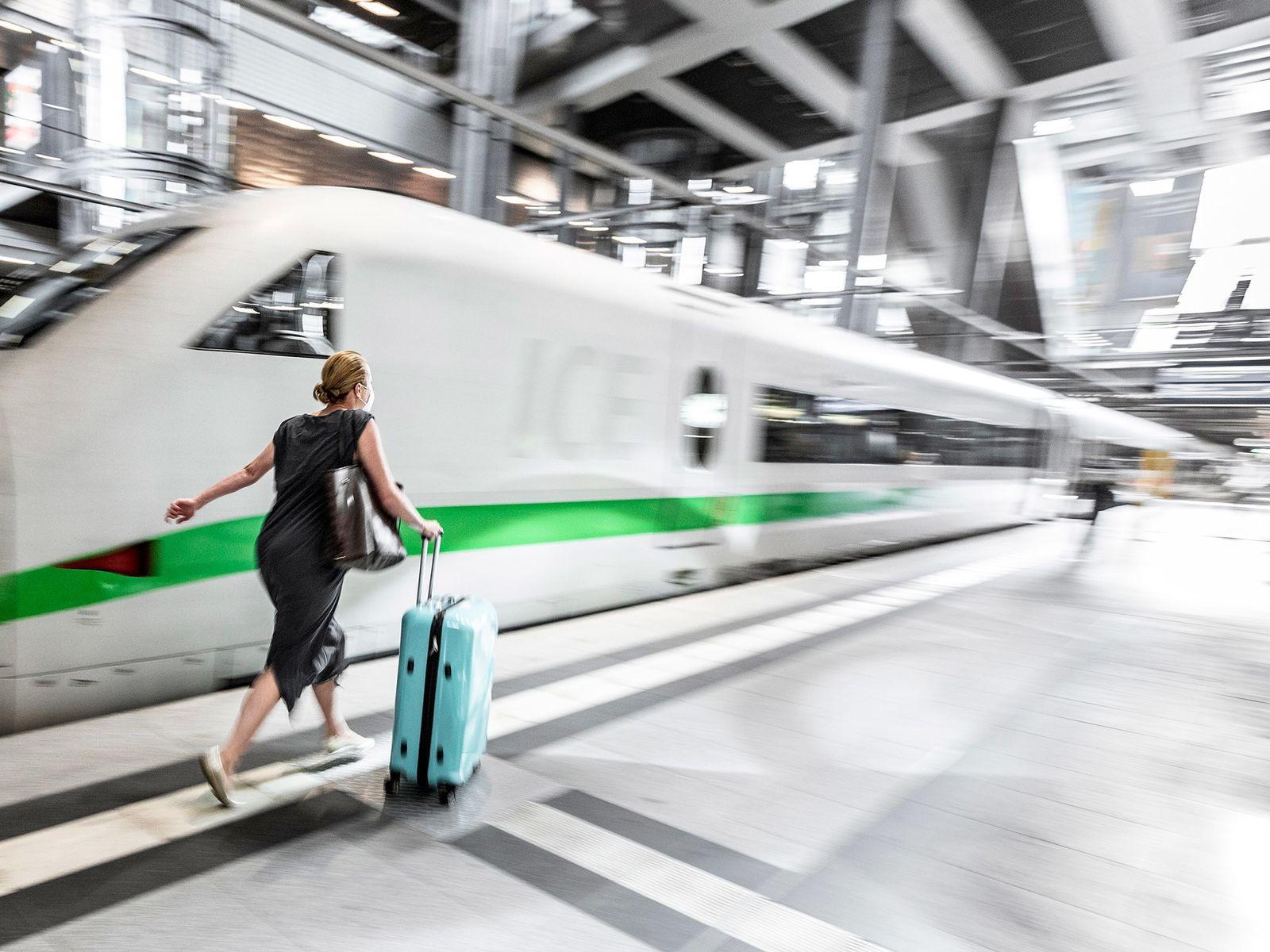 Uma viajante apressa-se para apanhar o comboio Intercidades Expresso de Inglaterra, na Estação Central Hauptbahnhof de ...
