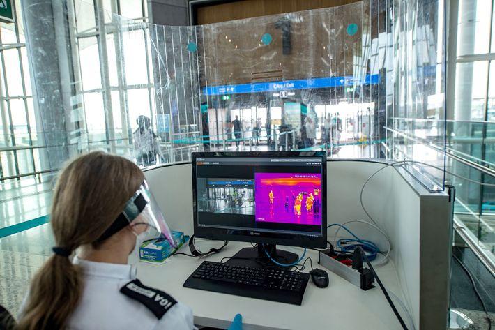Uma agente de segurança do Aeroporto de Istambul usa um monitor térmico para medir a temperatura ...