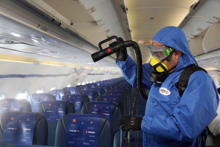 Um trabalhador com equipamento de proteção desinfeta um avião da Asrair Airlines no Aeroporto Internacional Ben ...