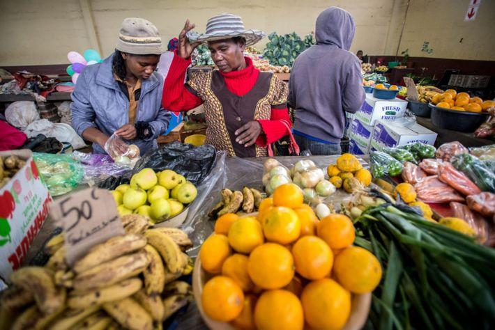 Mulheres compram produtos no mercado de atacado de produtos e artesanato Manzini em eSwatini, África.