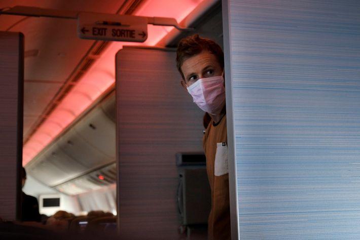 Um passageiro com máscara num voo entre Vancouver, no Canadá, e Sydney, na Austrália, na primavera ...
