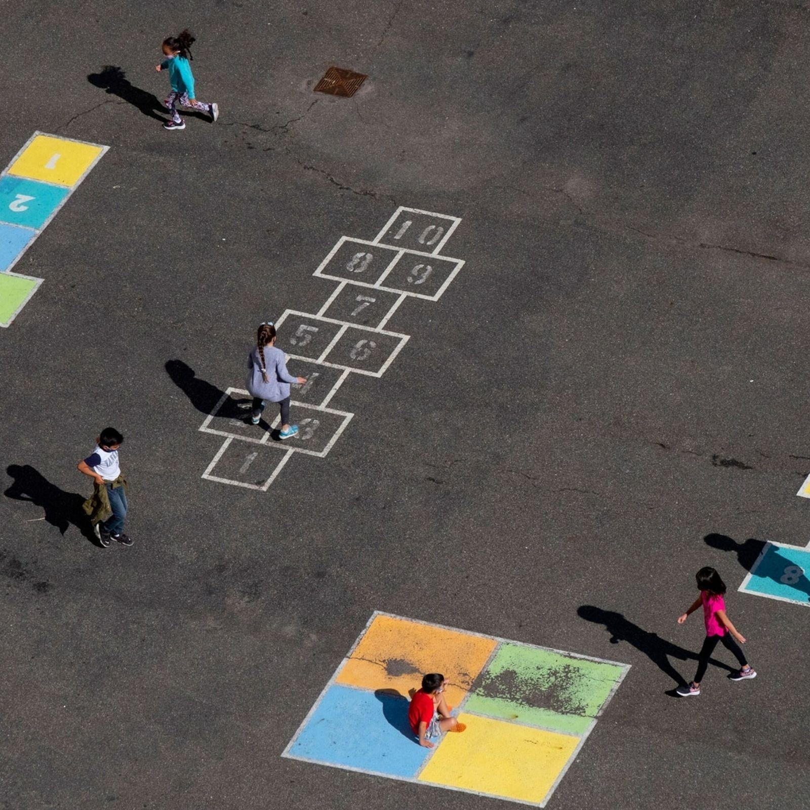 Grupo de crianças brinca ao ar livre com distanciamento social