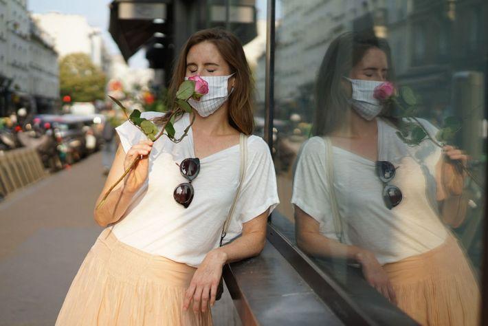 Uma mulher com uma máscara de proteção cheira uma rosa nas ruas de Paris.