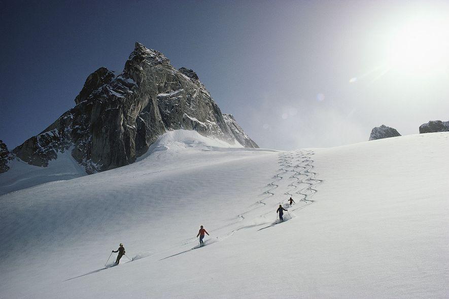 Um grupo de esquiadores desce o glaciar Vowel, na zona de esqui das Bugaboos, na Colúmbia Britânica.
