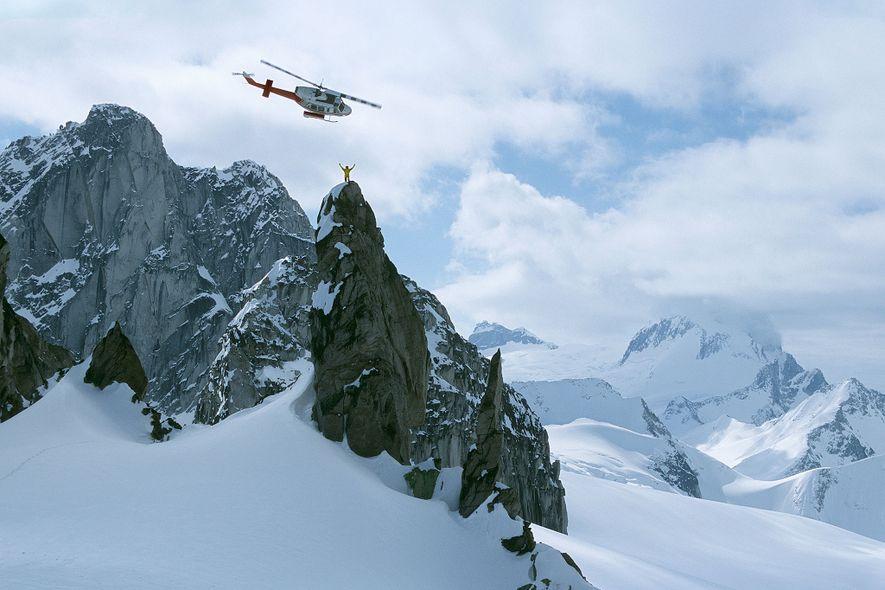 Um guia de heliesqui no topo do Osprey Spire, nas montanhas Purcell, no Canadá.