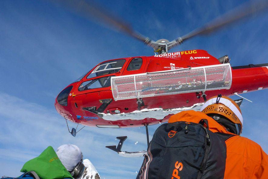 Um helicóptero afasta-se após deixar um grupo de heliesquiadores na península Tröllaskagi, na Islândia.