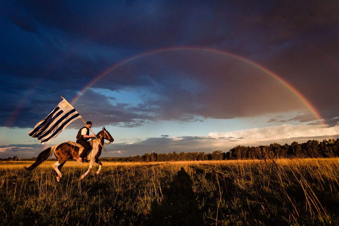 No Uruguai, um cavaleiro galopa sob um arco-íris duplo, com a bandeira azul e branca do ...