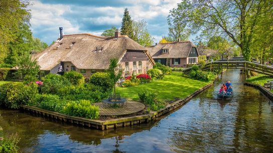 Um barco contornando um canal em Giethoorn, uma aldeia holandesa construída em pequenas ilhas de turfa, ...