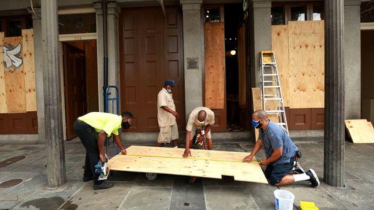 No domingo, dia 23 de agosto, trabalhadores selavam as janelas das casas e lojas no Quarteirão ...
