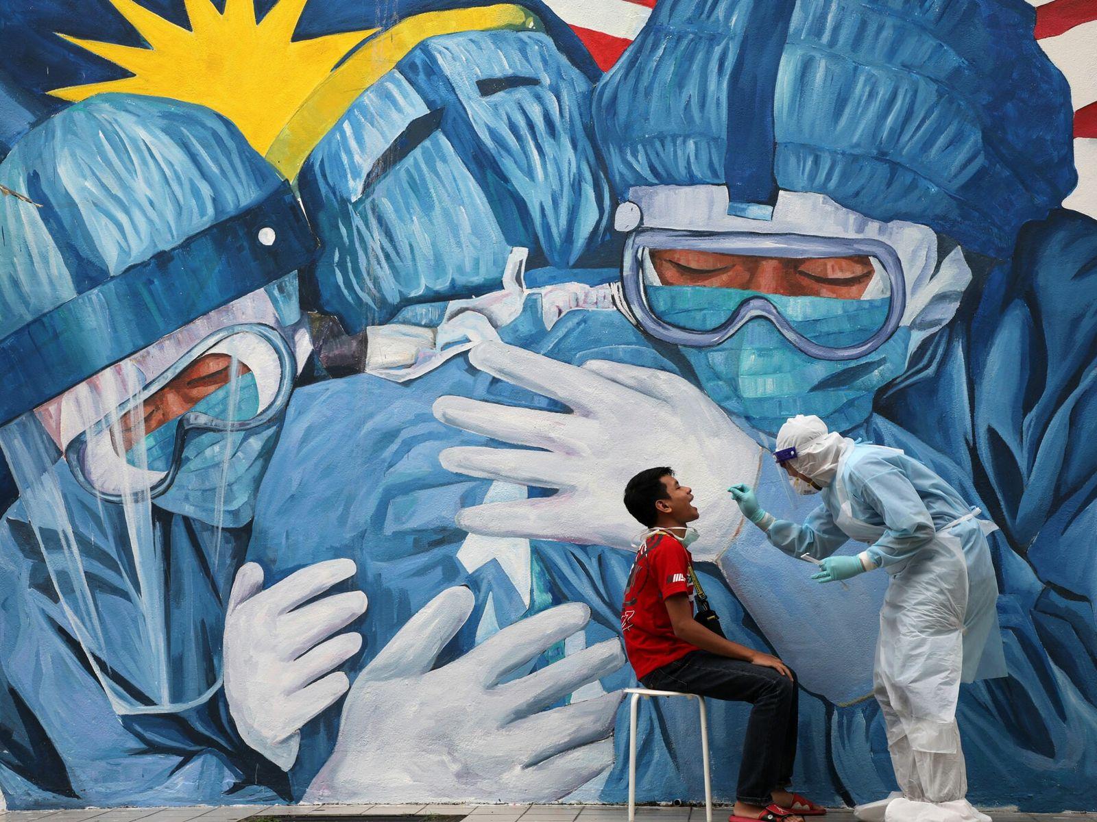 Um médico recolhe uma amostra com zaragatoa para um teste COVID-19 no exterior da Clínica Ajwa ...