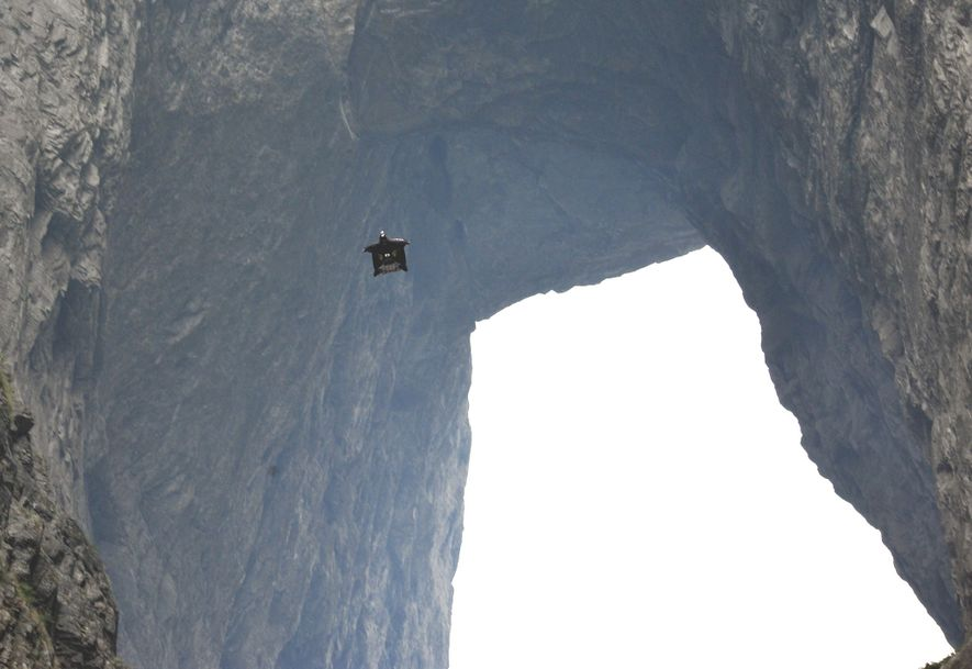 Corliss voa num wingsuit pela caverna de Tianmen no Parque Florestal Nacional de Tianmen na China, ...