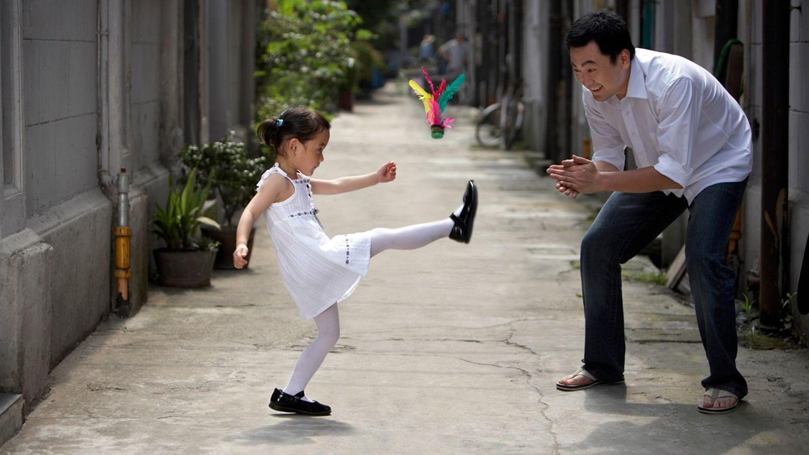 Uma menina e o pai jogam jegi chagi, um jogo sul coreano tradicional.