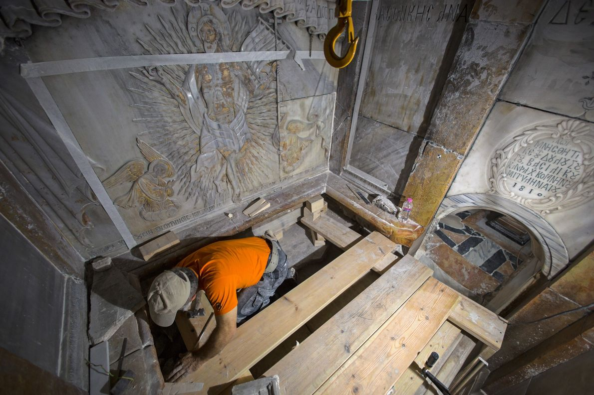 A conservator cleans the surface of the stone slab venerated as the final resting place of ...