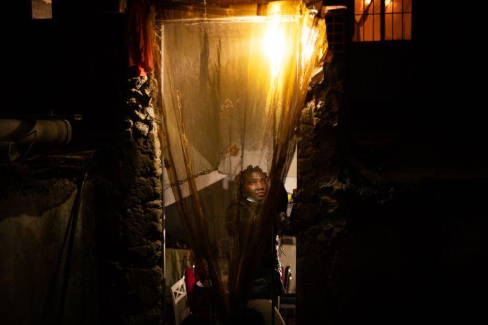 Telma Reis, 36 anos, abre a cortina da casa onde mora com os três filhos.