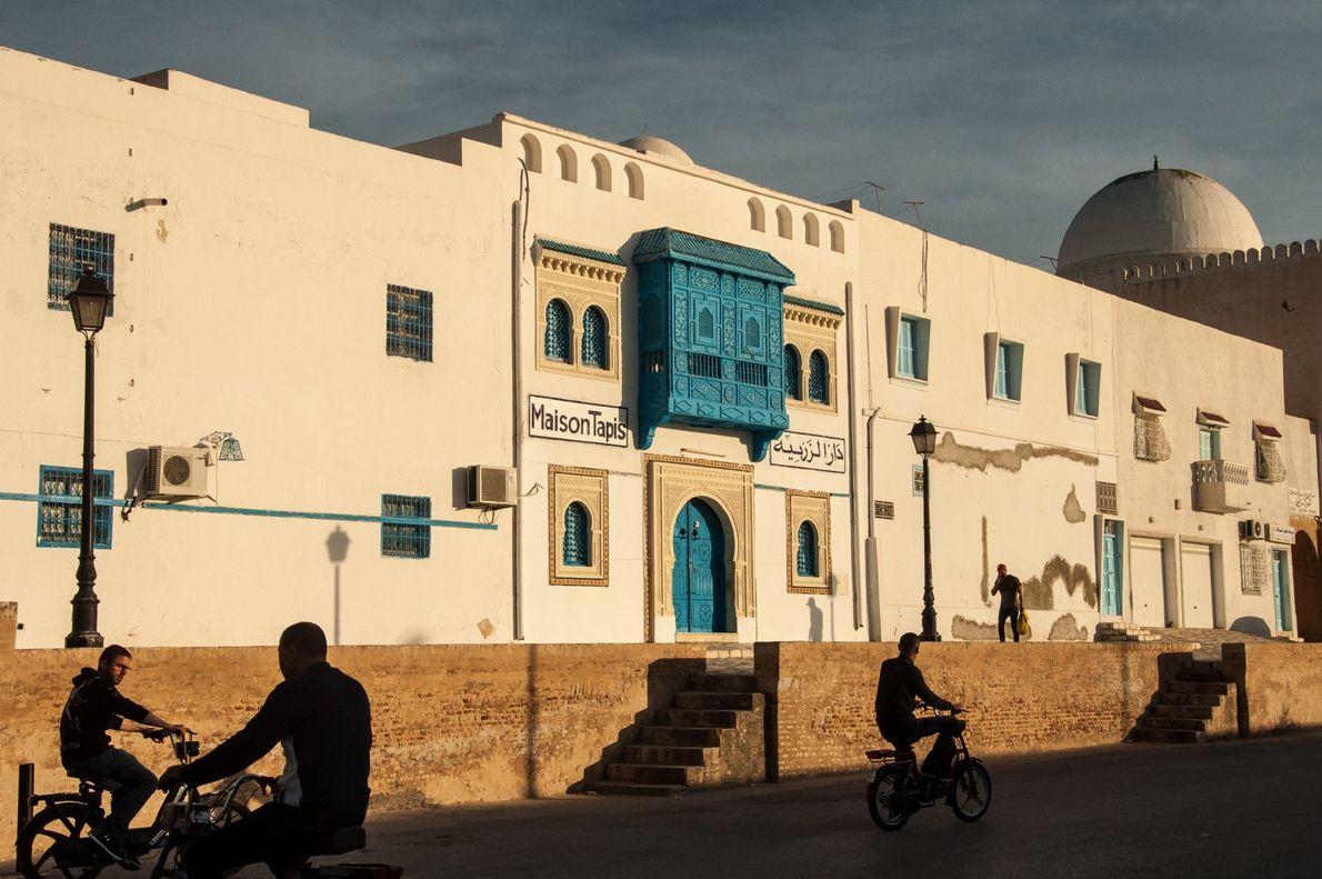 Ciclistas a passar em frente a uma loja de tapetes e souvenirs na cidade de Kairouan, ...