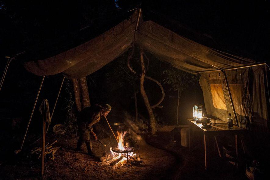 David Miner aviva o lume de uma fogueira noturna numa zona de acampamento da Ragati Conservancy. ...