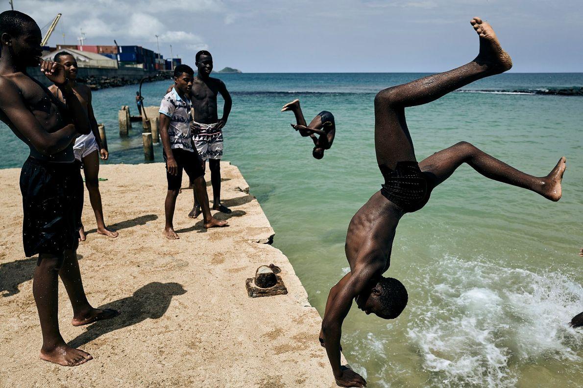 Rapazes mergulham no Golfo da Guiné para nadar na ilha de São Tomé, a cerca de ...
