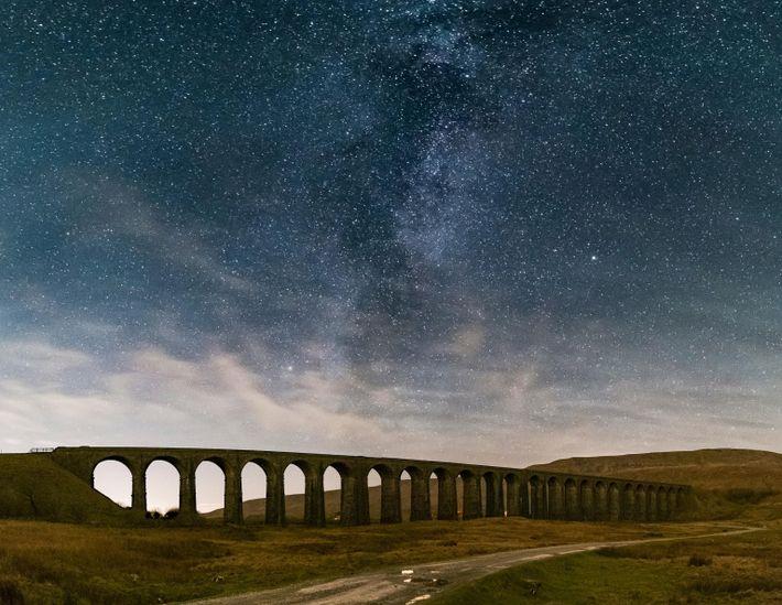 A Via Láctea eleva-se por cima do histórico Viaduto Ribblehead em North Yorkshire, Inglaterra.