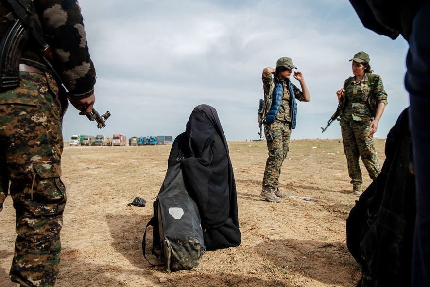 Combatentes curdos cercam uma mulher que se rende enquanto o ISIS abandona a cidade de Baghouz, ...