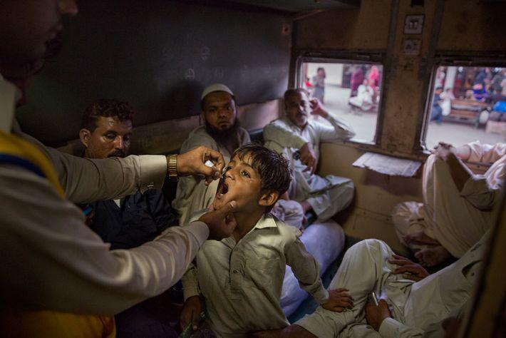 À procura de pessoas sem vacinas em Karachi, no Paquistão, um profissional de saúde encontra um ...